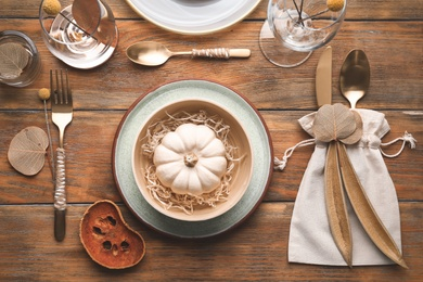 Autumn table setting with pumpkin and decor on wooden background, flat lay