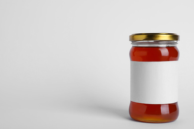 Glass jar of wildflower honey with blank label isolated on white