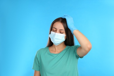Stressed woman in protective mask on light blue background. Mental health problems during COVID-19 pandemic