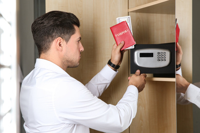 Man opening black steel safe with electronic lock at hotel