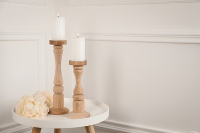 Elegant candlesticks with burning candles and flower on white table. Space for text