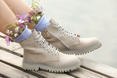 Woman sitting on wooden pier with flowers in socks outdoors, closeup