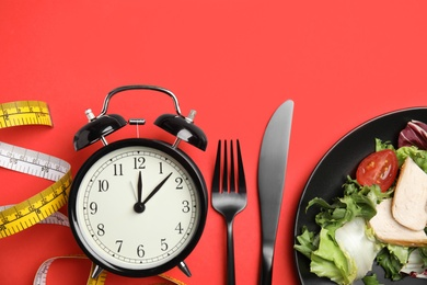 Plate of tasty salad, cutlery, alarm clock and measuring tape on red background, flat lay. Nutrition regime