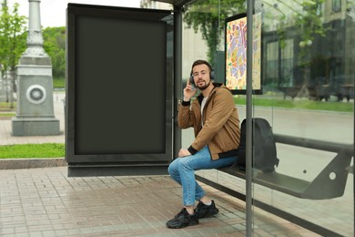Young man listening to music while waiting for public transport at bus stop