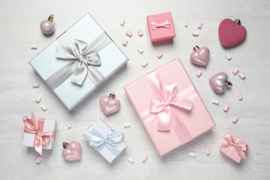 Beautiful gift boxes and festive decor on white table, flat lay