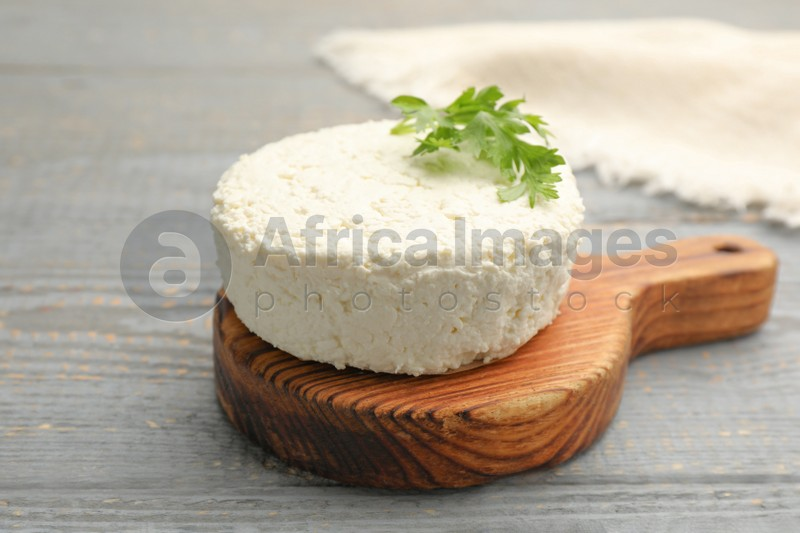 Delicious fresh cottage cheese with parsley on grey wooden table, closeup