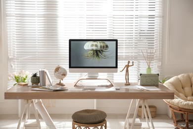 Stylish home office interior with comfortable workplace and papasan chair