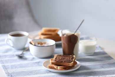Delicious breakfast with toasts and chocolate paste on table