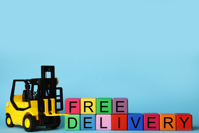 Toy forklift and cubes with words FREE DELIVERY on light blue background, space for text. Logistics and wholesale concept