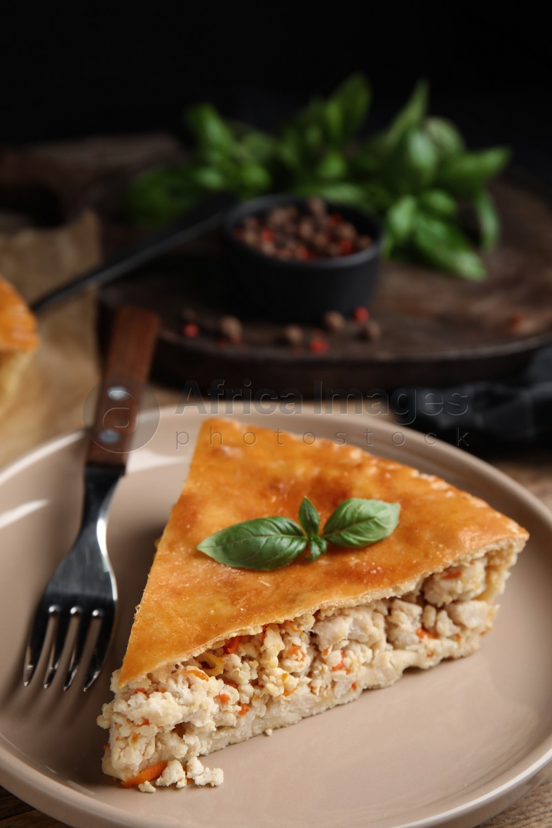 Piece of delicious pie with meat and basil on wooden table