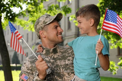 Soldier and his little son with American flags outdoors. Veterans Day in USA