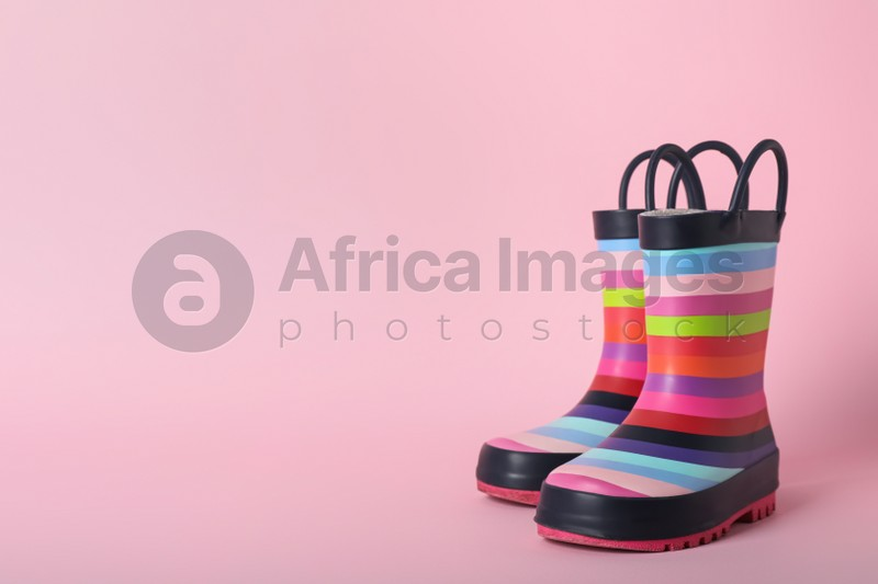 Pair of rainbow rubber boots on pink background. Space for text