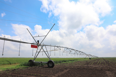 Modern irrigation system in field under cloudy sky. Agricultural equipment