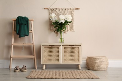Room interior with wooden chest of drawers near beige wall