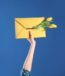 Woman holding elegant clutch with spring flowers on blue background, closeup