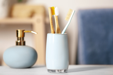 Bamboo toothbrushes in holder on light table indoors, closeup