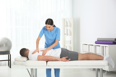 Doctor working with patient in hospital. Rehabilitation massage