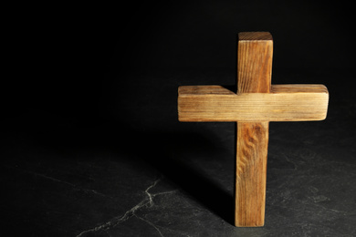 Wooden Christian cross on black slate table against dark background, above view with space for text. Religion concept