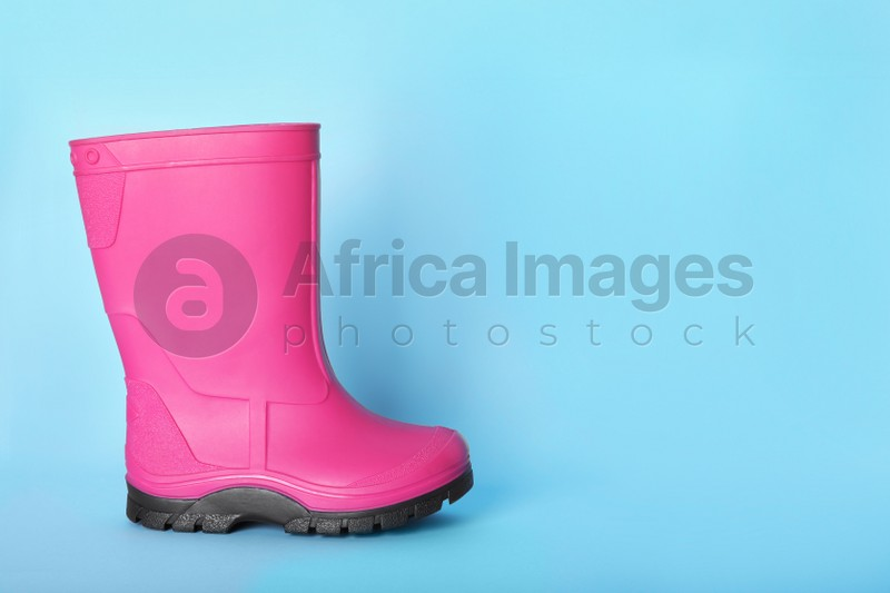 Bright pink rubber boot on light blue background. Space for text
