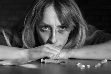 Addicted woman at table with different drugs, black and white effect