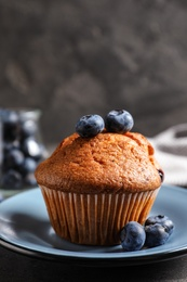 Plate with tasty muffin and blueberries on grey table, closeup
