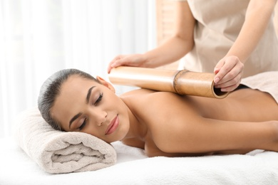 Young woman having massage with bamboo stick in wellness center