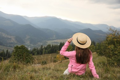 Young woman enjoying beautiful mountains landscape, back view. Space for text