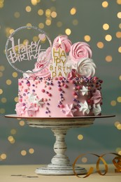 Beautiful birthday cake with festive decor and candle on white table