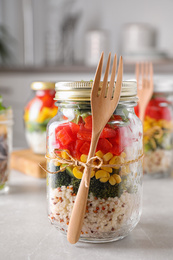 Glass jar with healthy meal on light grey marble table
