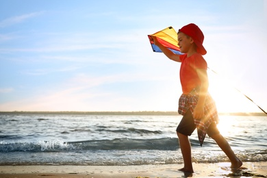 Cute little child with kite running on beach near sea at sunset. Spending time in nature