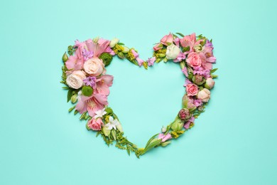 Beautiful heart shaped floral composition on turquoise background, flat lay