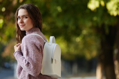 Young woman with stylish white backpack in park, space for text