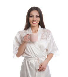 Young woman in silk robe with cup of beverage on white background