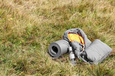 Grey sleeping bag, camping mat and bottle on green grass outdoors, space for text