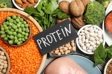Card with word PROTEIN and different products on table, flat lay