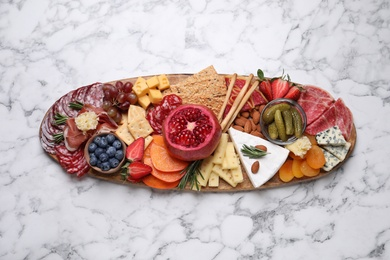 Wooden plate with different delicious snacks on white marble table, top view
