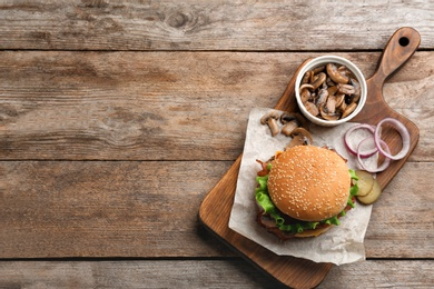 Tasty burger and mushrooms on wooden background, top view. Space for text