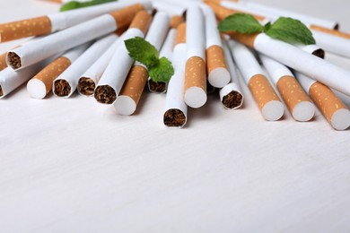 Menthol cigarettes and mint on white wooden table. Space for text