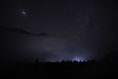 Beautiful view of misty mountains under starry sky at night