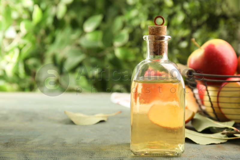 Natural apple vinegar and fresh fruits on blue wooden table. Space for text