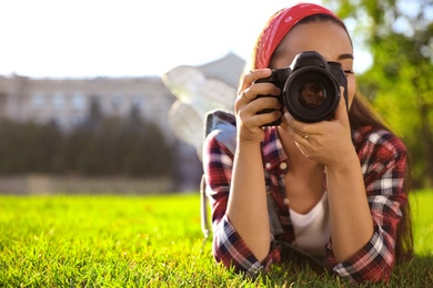 Young photographer taking picture with professional camera on green grass. Space for text