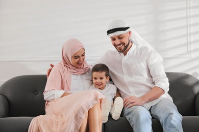 Happy Muslim family spending time together on sofa at home