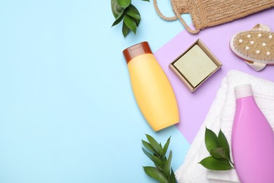 Flat lay composition with shower gel bottles and green leaves on color background, space for text