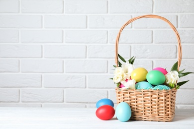 Wicker basket with bright painted Easter eggs and spring flowers on white wooden table near brick wall. Space for text