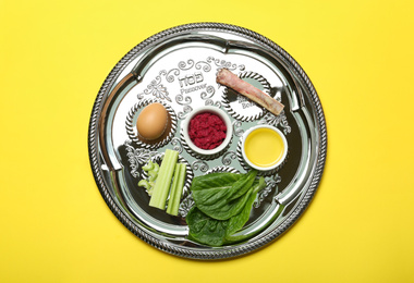 Passover Seder plate (keara) with symbolic meal on yellow background, top view. Pesah celebration