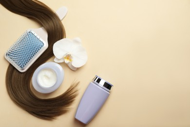 Natural cosmetic products, orchid flower, brush and hair lock on beige background, flat lay. Space for text