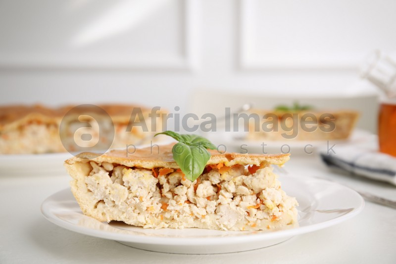 Piece of delicious pie with meat and basil on white table