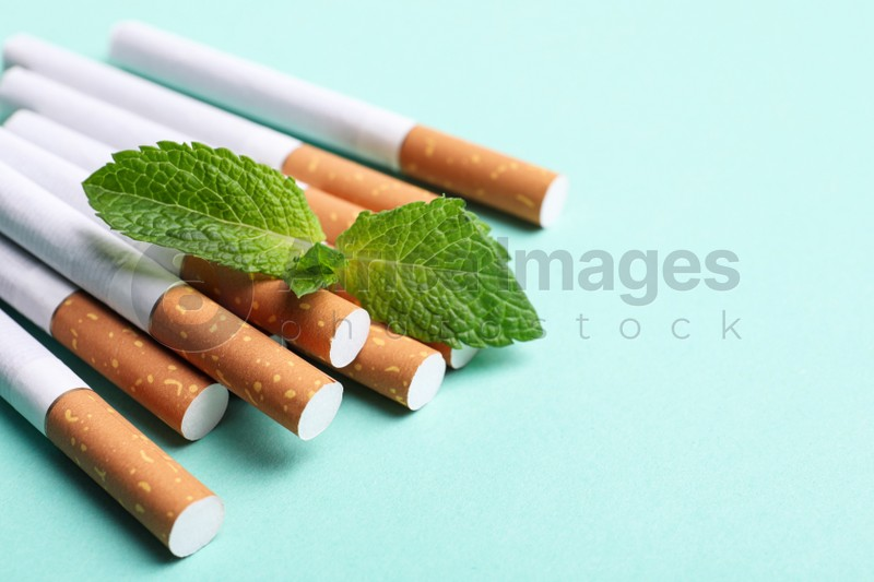 Menthol cigarettes and mint on turquoise background, closeup. Space for text