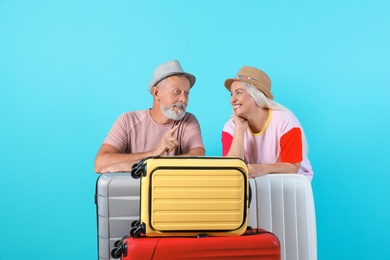 Senior couple with suitcases on color background. Vacation travel
