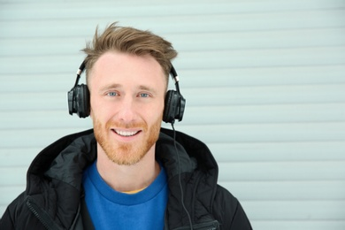 Young man listening to music with headphones against light wall. Space for text